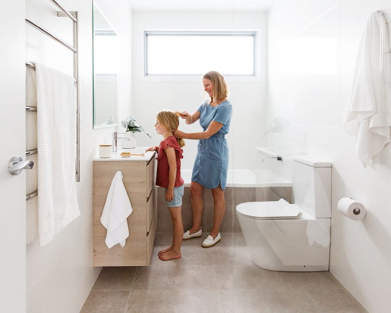 mother brushing daughter's hair inside a modern white and light bathroom renovation with a Milu Odourless back-to-wall toilet