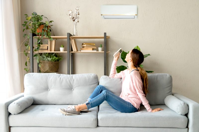 yound woman turning off air conditioning unit with a remote control while she sits on the couch