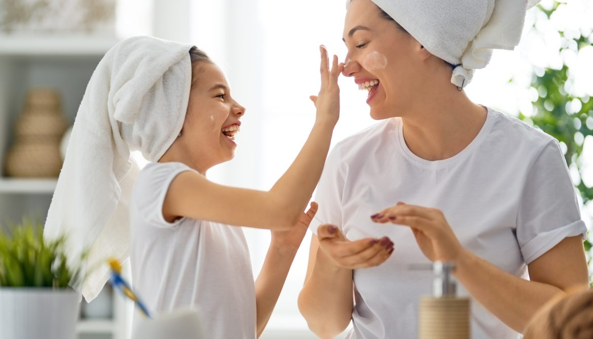 mother and daoughter in the bathroom, laughing as daughter puts cream on mother's nose