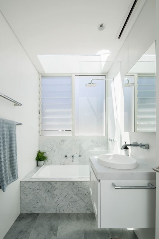 The Linear Slot Grille sits over the bath and shower in this renovated family bathroom