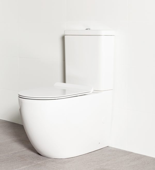 Milu Odourless Crest back-to-wall toilet angled side view with toilet seat down. Positioned against white tiled wall on warm grey coloured floor tiles