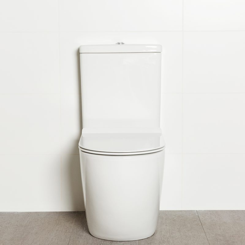Milu Odourless Crest back-to-wall toilet front view with toilet seat down. Positioned against white tiled wall on warm grey coloured floor tiles