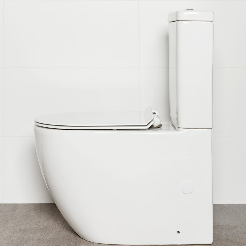 Milu Odourless Crest back-to-wall toilet side view with toilet seat down. Positioned against white tiled wall on warm grey coloured floor tiles