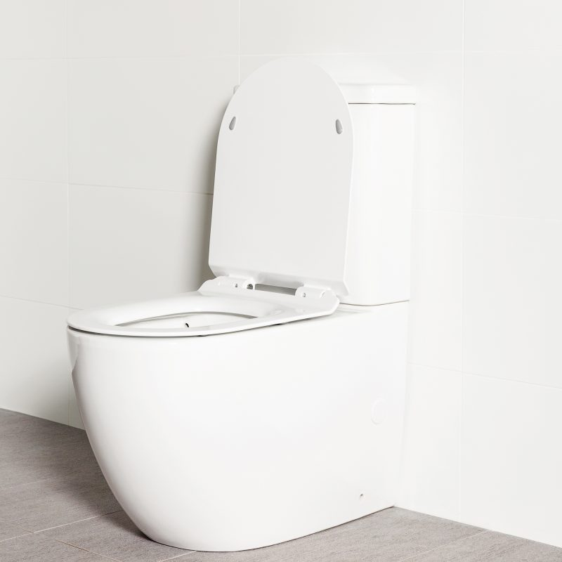 Milu Odourless Crest back-to-wall toilet angled side view with toilet seat up. Positioned against white tiled wall on warm grey coloured floor tiles