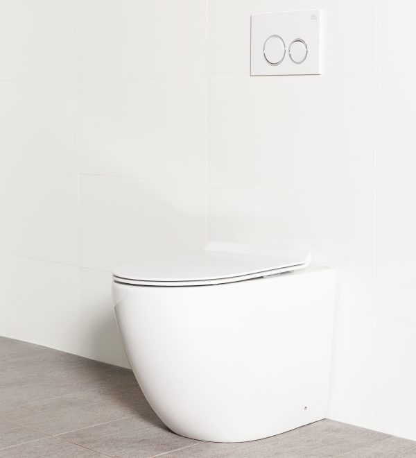 Milu Odourless Crest in-wall floor mounted toilet angled side view with white flush plate. Positioned against white tiled wall on warm grey coloured floor tiles