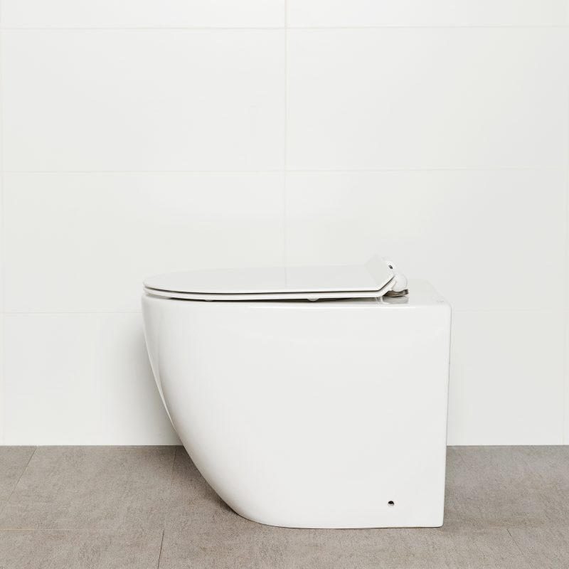 Milu Odourless Crest in-wall floor mounted toilet side view with toilet seat down and white flush plate. Toilet has curved pan and minimal design