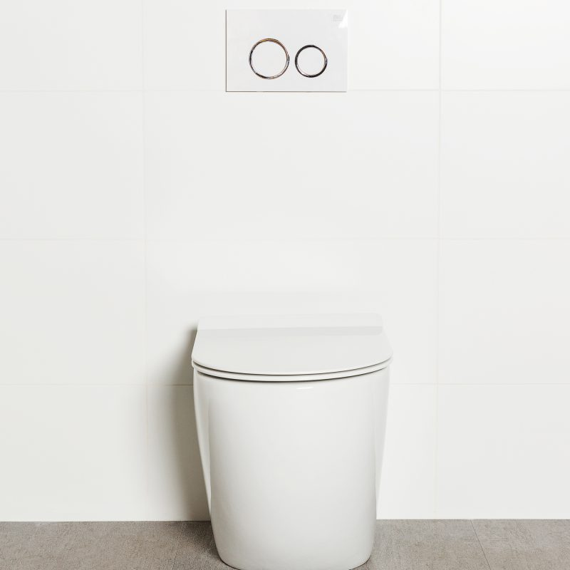 Milu Odourless Crest in-wall floor mounted toilet front view with white flush plate. Toilet has curved pan and minimal design
