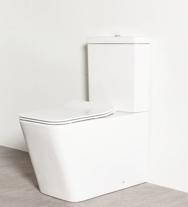 Milu Odourless Form back-to-wall toilet has a modern rectangular design, it is photographed against a white tiled bathroom wall
