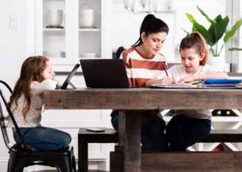 mother and two daughters sitting at kitchen table working and home schooling