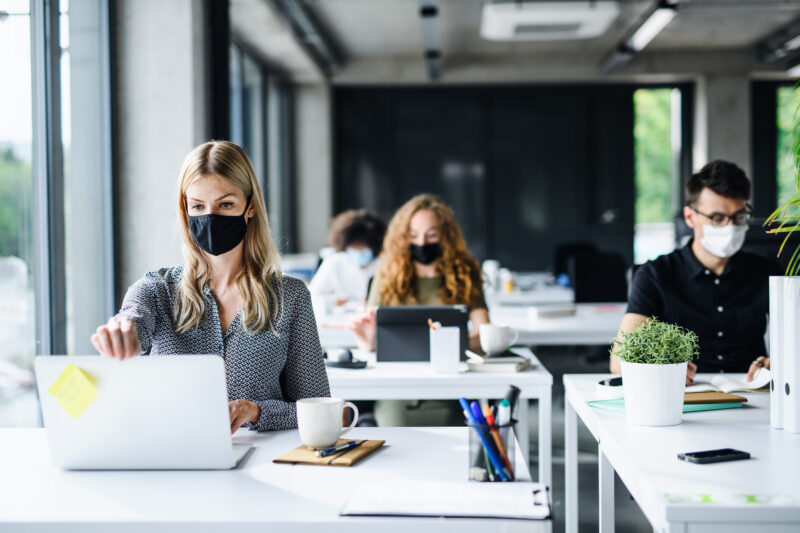 three people working in a modern office wearing masks