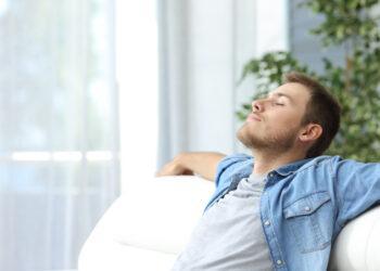 man relaxing on the sofa enjoying fresh air in his home