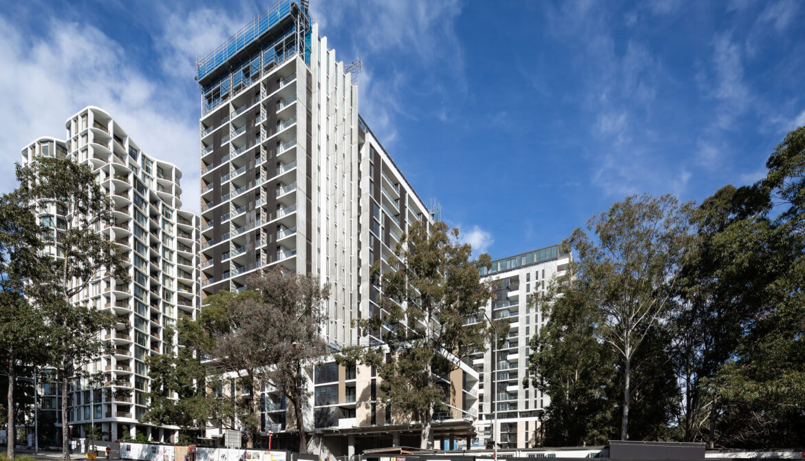 External view of the Nature Macquarie Park development, image Showa the a multi story residential tower against a bright blue sky