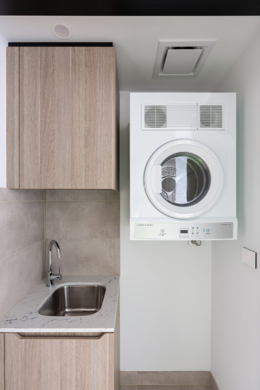 The laundry space in a Natura apartment with Expella's Ceiling Fan shown above the dryer