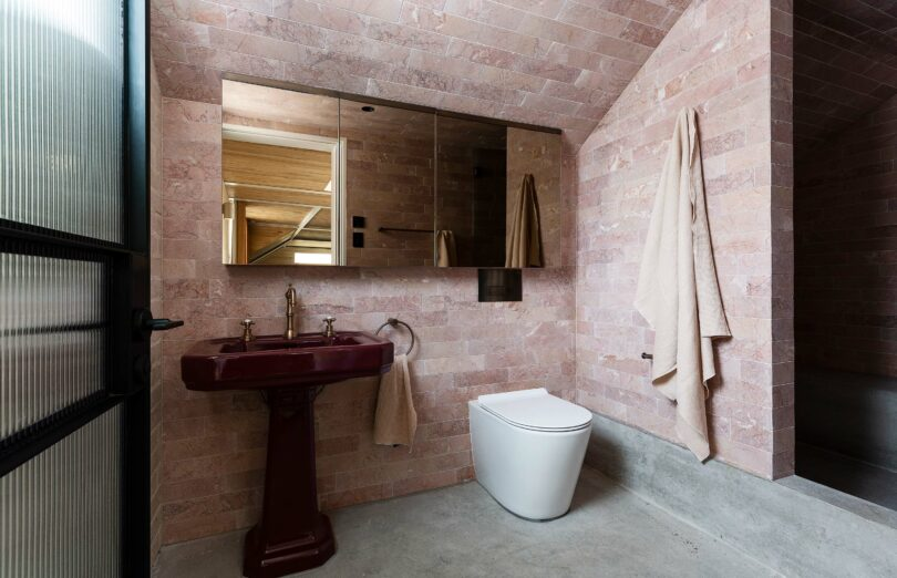 Loft bathroom in Alexander House featuring Expella's Milu Odourless toilet and pink marble Rosso Cream Tiles